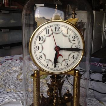 A glass dome encased brass clock the square mechanism - Clocks