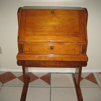 a character in a movie  a drop leaf secretary made of cedar sitting on a trestle base.