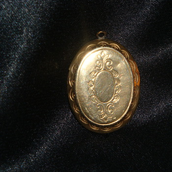 Locket   Does anyone know the date on this?  Is it Brass, gold?  Worth?