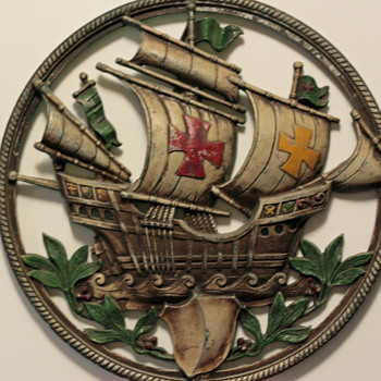 A round cast metal wall hanging of a ship