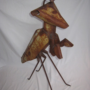 rustic folk art sculpture of a praying Mantis