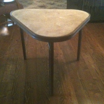 This is a triangular card table.  The legs fold up and the corners are curved.  The top is velvet.