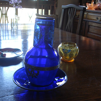 A cobalt glass bottle, saucer and beacker