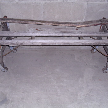 Wooden bench with metal wheels.