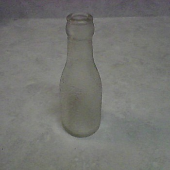 A SMALL OVERSHOT GLASS BOTTLE