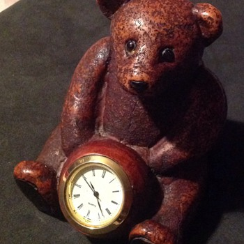 Resin teddybear holding a watch