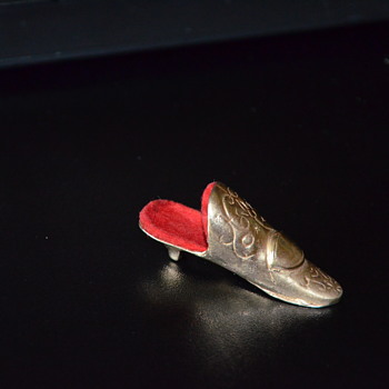 Tiny gold-colored metal slipper lined with felt