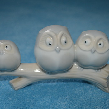 Porcelaine owls sitting on branch