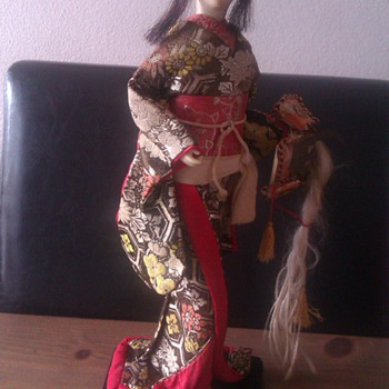 Old geisha doll with samurai helmet