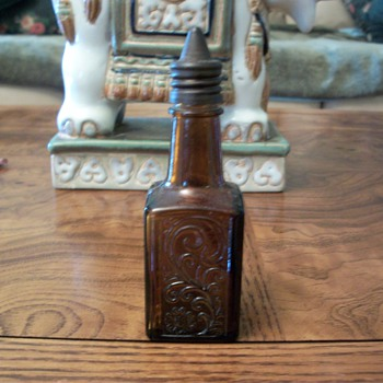 small brown square very detailed bottle with pointed metal screw on cap
