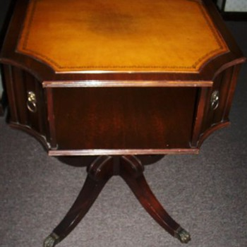 antique table with leather top and convex corners.