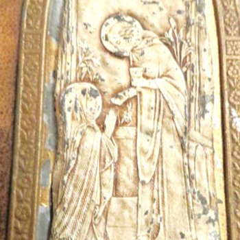 religious metal icon of a woman giving communion to the virgin Mary