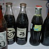 A small collection of Full Coca Cola anniversary bottles