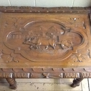 Side table with a carved scene and glass tray top