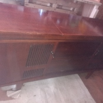 A radiogram side board, unknown date and maker, 5ft long all wood with rising speaker tops, central swivel shelf type effort