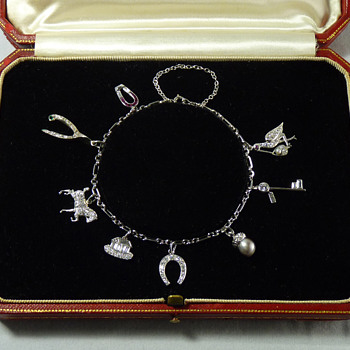 Help identifying maker of Art Deco Platinum and Diamond Charm Bracelet