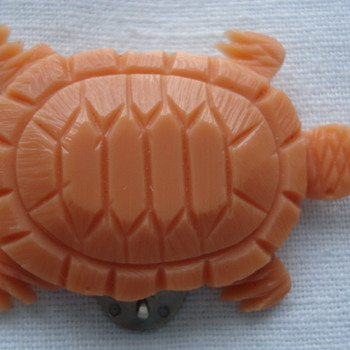 An early plastic dress clip like a little coral turtle