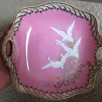 Flying swans on pink dish