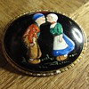 An enamal brooch with couple in traditional costumes