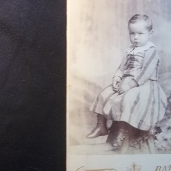 LITTLE BOY IN WELL MADE DRESS,LOOKS SOBER ABOUT HAVING HIS PICTURE TAKEN