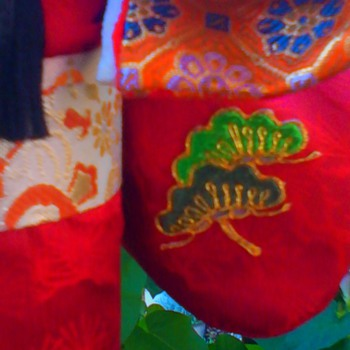Flute player with bonsai pine branch detail on sleeve (continued)