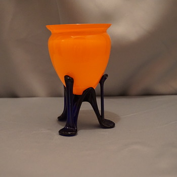 "Orange glass vase 5"" tall with 3 cobalt blue legs"