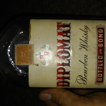 Diplomat bourbon whiskey with authentic department of liquor control stamps and seal over cap.