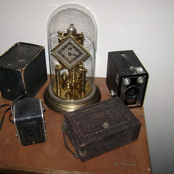 Small camera collection and grandmas clock.