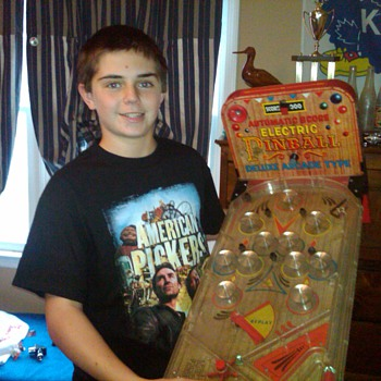 James with his small electric pinball game - Games