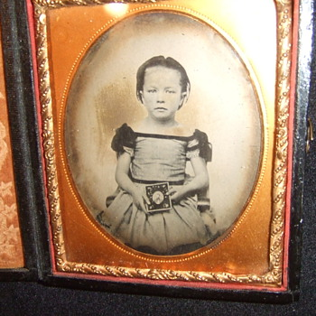 Child holds a photograph of a man - Photographs