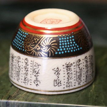 Sake cup with writing all over it