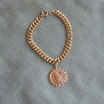 Unusual solid gold bracelet and charm (medal?)