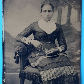 Tintype photo of Lady holding a locket or watch.