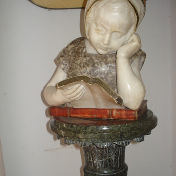 A marble sculpture of a little girl learning to read called Irene - Visual Art