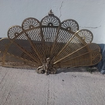 A quite dramatic fire screen in brass A Peacock expanding fan type fire screen