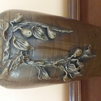 Brown glazed pottery with applied leaves and berries