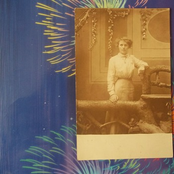 REAL PHOTO POSTCARD, c.1913 WONDERFUL BACKDROP & SET UP FOR THIS CHARMING YOUNG WOMAN'S PHOTO.