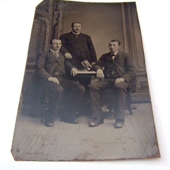 Tintype of men with stereoscope and card on table