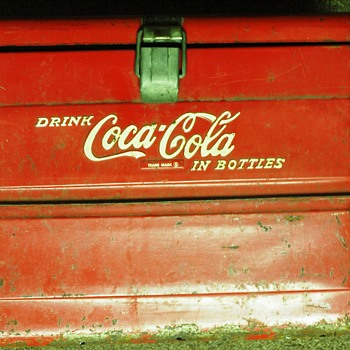 Small (roughly 16 x 12 x 10) cooler w/ 2 hinges on back, one latch on front, simple metal handle on top.   - Coca-Cola