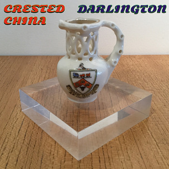 CRESTED CHINA DARLINGTON PUZZLE JUG.