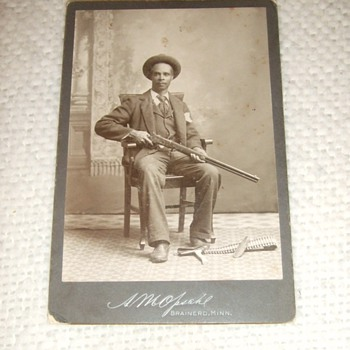 Cabinet card of African American Man with Winchester Rifle