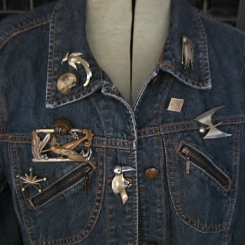 Silver, bronze, butterfly, pebble, military & other pins on jean jacket
