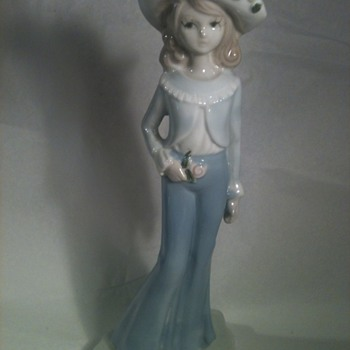 A PORCELAIN GIRL WITH BIG PANTS AND BIG HAT .