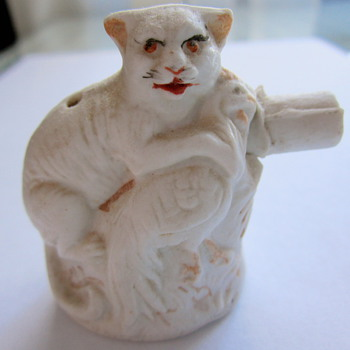 "What is this cat with chicken porcelain ""thing""?"
