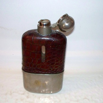 Cut glass flask with leather covering and a removable cup...silver