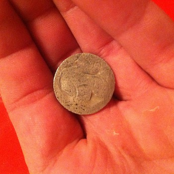 I'm not sure but I think this is a jefferson nickel stamped of standing liberty on a silver plachet.      Any ideas? - US Coins