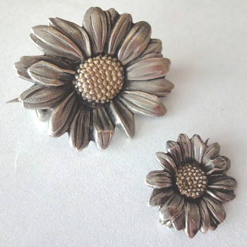 Two antique Silver Daisy brooches with gold(?) heart.