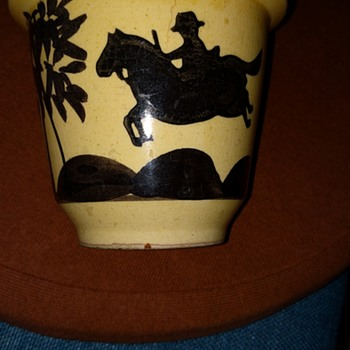 Flower pot with interesting man riding a horse with a tree