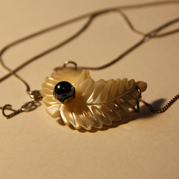 Carved shell leaf with black pearl