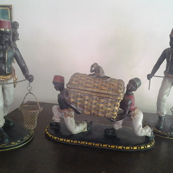 wooden carvings of black coffee pickers